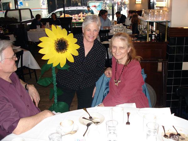 Carol Lee presents Nancy Willard with a sunflower
